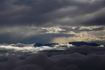 光射す雲間の中央アルプス Photo by Kenji Shimadate