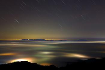 雲海下の街明かり Photo by Kenji Shimadate